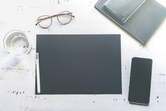 Model van leeg zwart document blad, smartphone, oogglazen, op natuurlijk wit authentiek houten bureau Bedrijfs lege spot royalty-vrije stock foto's