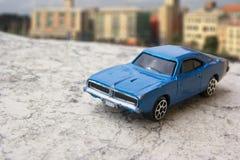 Model of vintage blue car. Toys: Blue vintage car model with city in background Stock Images