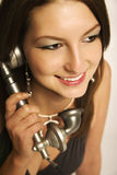 Model with vintage telephone. Young female model calling on an antique telephone, smiling royalty free stock photo