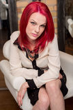 Model with Vivid Red Hair in Chair Royalty Free Stock Image