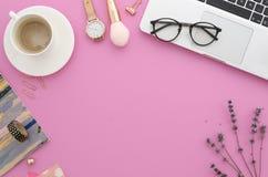 Model Vrouwelijke werkruimte met laptop, lavendel, make-uptoebehoren, notitieboekje, glazen, koffie Vlak leg vrouwen` s bureau stock fotografie