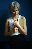 Model w srebnej peruce pozuje z książką z bliska niebieska tła Fotografia Stock