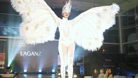 Model w szyk masce w białym kostiumu z skrzydłami i chodzi along na pasie startowym przy eleganckim wydarzeniem zbiory