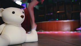 Model walking legs in soft slippers walk on floor in nightclub. Plush bear toy stock video footage