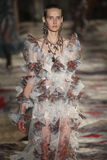 A model walks the runway during the Alexander McQueen designed by Sarah Burton show. PARIS, FRANCE - OCTOBER 3: A model walks the runway during the Alexander Stock Image