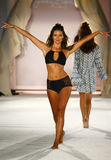 A model walks runway in designer swim apparel during the Frankies Bikinis fashion show. MIAMI, FL - JULY 18: A model walks runway in designer swim apparel during royalty free stock image