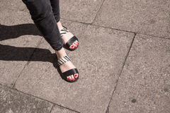 Model wearing black and white sandals with zebra print. Red nail varnish on toes and skinny black jeans. Focus on woman legs and feet royalty free stock photos