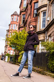 Model wearing blue skinny jeans, black sneakers and sunglasses. In a British street with tenements victorian flats in the background Royalty Free Stock Image