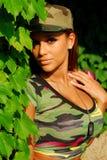 Model wearing camouflage tee-shirt. Beautiful model wearing a camouflage tee shirt and hat royalty free stock image