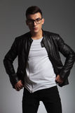 Model wearing glasses in studio fixing his jacket. Sexy model wearing glasses posing in studio background fixing his leather jacket while looking at the camera Royalty Free Stock Image
