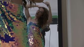 Model wearing a glitter dress combing her hair in the mirror in a professional studio before the photo session -. White attractive fashion model wearing a stock footage