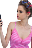 Model wearing hair rollers posing looking at the phone Royalty Free Stock Image