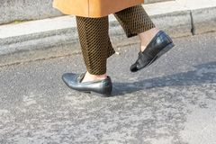 Model wearing a pair of spotted pants, a pair of moccasins without socks and a brown leather overcoat royalty free stock photo