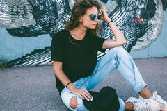 Model wearing plain tshirt and sunglasses posing over street wall. Model wearing plain black t-shirt, boyfriend jeans, sneakers and hipster sunglasses posing royalty free stock images