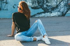 Model wearing plain tshirt and sunglasses posing over street wall. Model wearing plain black t-shirt, boyfriend jeans, sneakers and hipster sunglasses posing stock photo