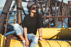 Model wearing plain tshirt and sunglasses posing over street wal Stock Image