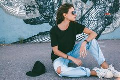 Model wearing plain tshirt and sunglasses posing over street wall. Model wearing plain black t-shirt, boyfriend jeans, sneakers and hipster sunglasses posing royalty free stock photo