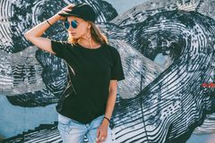 Model wearing plain tshirt and sunglasses posing over street wall. Model wearing plain black t-shirt, cap and hipster sunglasses posing against street wall, teen royalty free stock photos