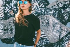 Model wearing plain tshirt and sunglasses posing over street wall. Model wearing plain black t-shirt and hipster sunglasses posing against street wall, teen stock photos
