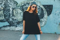 Model wearing plain tshirt and sunglasses posing over street wal. Model wearing plain black t-shirt and hipster sunglasses posing against street wall, teen urban Stock Photography