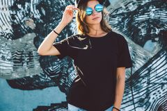 Model wearing plain tshirt and sunglasses posing over street wall. Model wearing plain black t-shirt and hipster sunglasses posing against street wall, teen royalty free stock photo