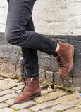 Model wearing skinny trousers and brown boots. Model legs wearing tight black skinny trousers and brown ankle boots. Black and white brick wall as a background Royalty Free Stock Images