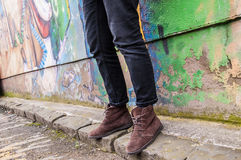 Model wearing skinny trousers and brown boots. Model wearing tight black denim skinny trousers and brown suede ankle boots and walking in front of a graffiti Royalty Free Stock Image
