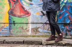Model wearing skinny trousers and brown boots. Model wearing tight black denim skinny trousers and brown suede ankle boots and walking in front of a graffiti Stock Image