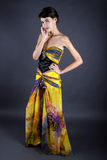 Model Wearing Tie Dye Yellow Dress. Woman wearing a yellow silk tie dye dress on a dark studio background Royalty Free Stock Photography