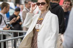 Model Wears A Pair Of Sunglasses, A White Jacket And A Jersey Royalty Free Stock Images