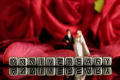 Model wedding couple with the word anniversary on beads and rose bouquet. Miniature scale model wedding couple with the word anniversary on beads and rose Stock Photo