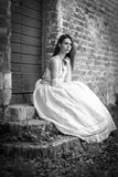 Model in wedding dress. Attractive elegant model posing in wedding dress on steps of old brick built (farm) building with weeds and dead leaves lying around Royalty Free Stock Photos