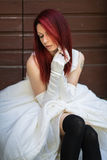 Model in wedding gown. A model with red hear, tattoos and piercings wearing white wedding dress with black stockings and gloves Stock Image