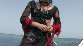 Model in white costume of pirate on ship near water in Red Sea. stock video