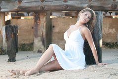 Model in a white dress at beach near a jetty. Stock Photography