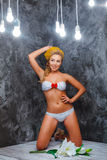 Model in a white knitted bikini stay near the bouquet of flowers Stock Photography