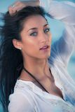 Model with white shirt against blue water Stock Photos