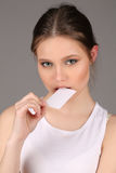 Model in white singlet bitting card. Close up. Gray background Royalty Free Stock Images
