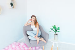 Model in white singlet and blue denim with holes sitting into the grey armchair. Royalty Free Stock Photos