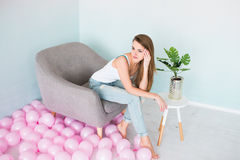 Model in white singlet and blue denim with holes sitting into the grey armchair. Stock Images