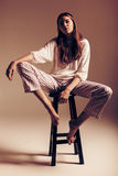 Model in white top and striped pants on chair. In studio at sunset Royalty Free Stock Image