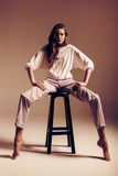 Model in white top and striped pants sitting on chair Royalty Free Stock Photos