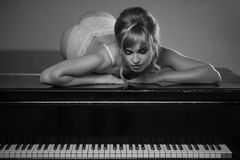 Model in white underwear posing on top of the piano. Awesome model in underwear posing on top of the piano for fashion shoot Stock Images