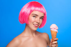 Model in wig posing with ice cream. Young smiling model wearing short pink wig holding ice cream cone and looking at camera on blue Royalty Free Stock Photography