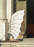 A model of a wing outside a building in Venice. A large white wing stands outside an old building in Venice Royalty Free Stock Photo