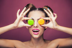 Model, a woman with bright make-up and colour biscuits joking. Royalty Free Stock Photography