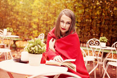 Model Woman Reading a Book in a Cafe Outdoors Royalty Free Stock Photo