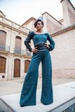 Model of women`s fashion poses standing with a trouser suit on the outside of the old town of a rural town royalty free stock images