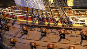 Model of wooden fighting ship of the 17th century against the backdrop of the reconstructed ship Vasa in the same museum. STOCKHOLM, SWEDEN - MAY 01, 2016: Model stock footage