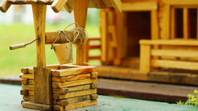 Model of the wooden house with a draw-well. Miniature of the village wooden house with a draw-well stock images